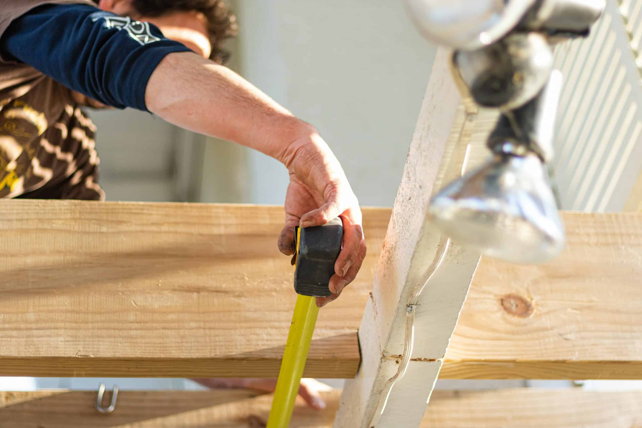man working on home with tape measure